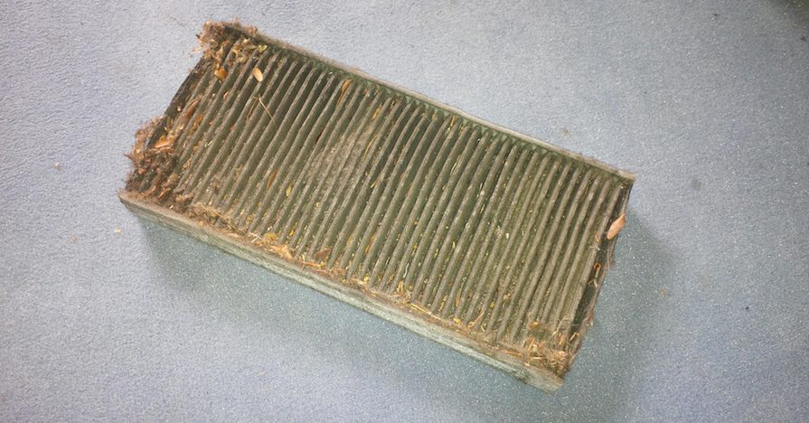 A dirty engine air filter is removed from a car. It's a large, rectangular metal component caked in dirt and debris.