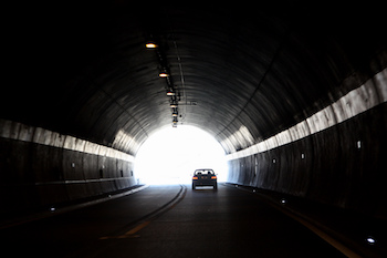 A car drives through a dark tunnel