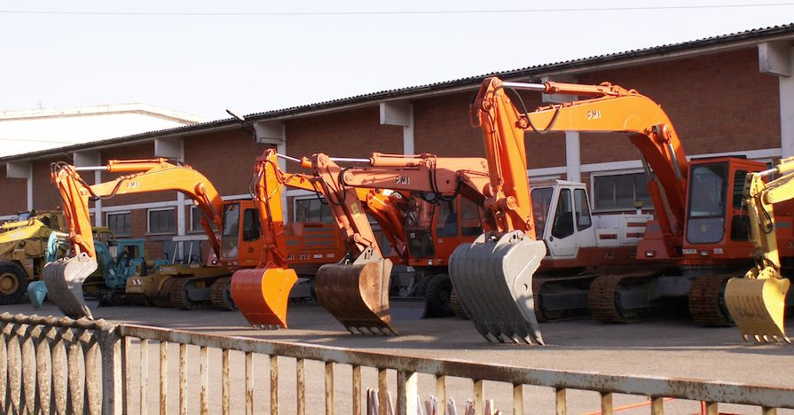Construction equipment is parked in a line. Operators will need heavy machinery safety tips.