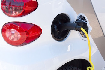 A close-up a gas nozzle going into a white hybrid car