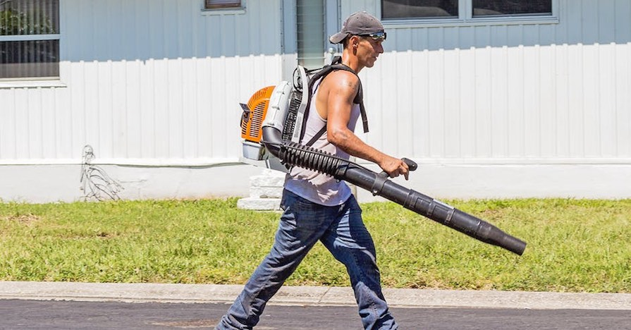 A man uses a leaf blower to clear landscape debris.