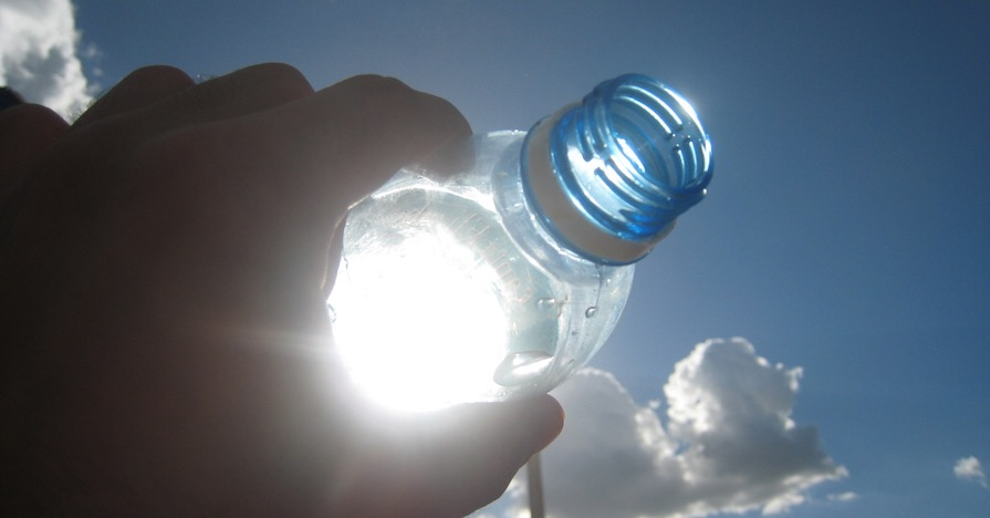 The sun reflects through a water bottle held in a person's hand.