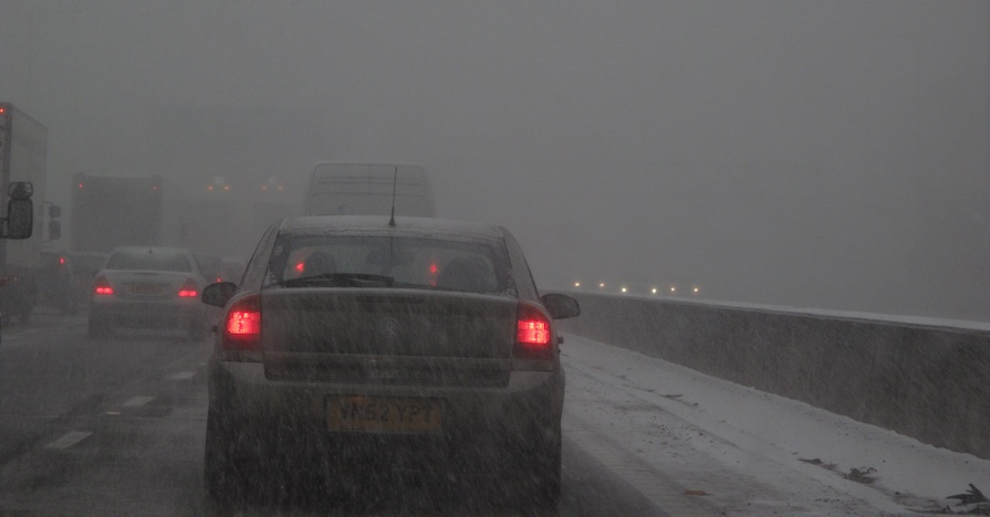 A highway during a blizzard. Use these four tips to avoid having a dead battery during the coldest months of the year.