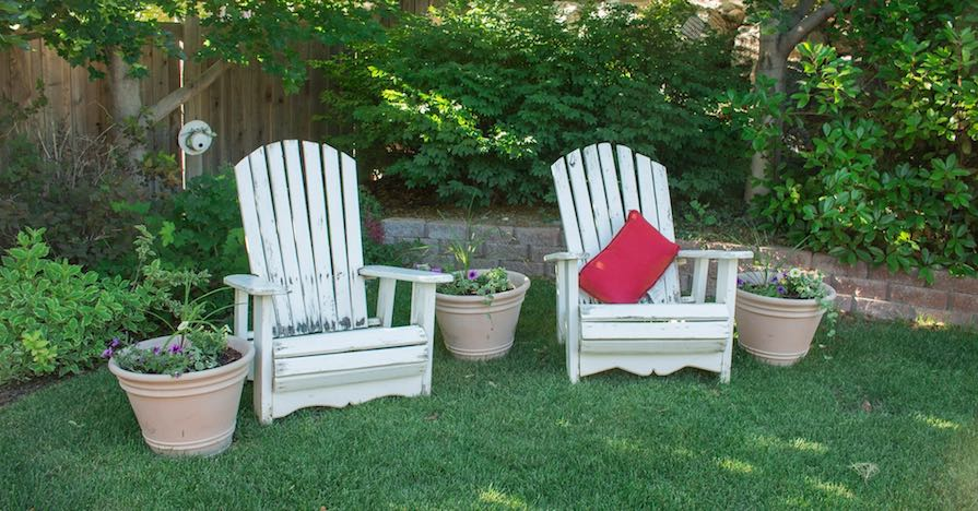 A lush backyard with lawn chairs. Before summer arrives, here's how you can get your lawn ready for the warmer months.