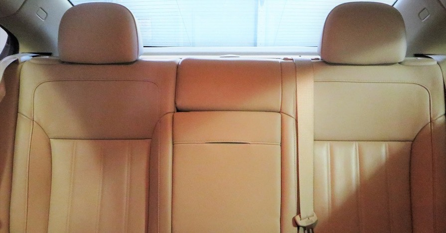 Clean, tan seats in the rear of a car's cabin.