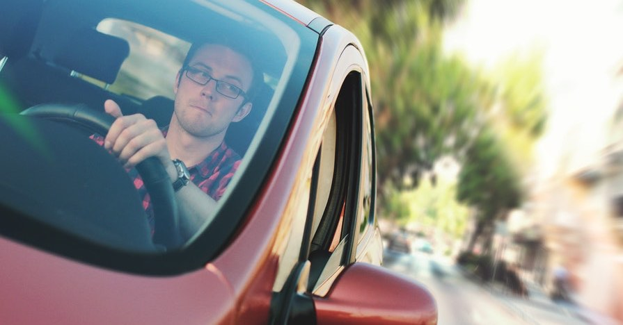 A driver behind the wheel of a car. Smelling gas in your car can be a sign of a major issue or a minor one. Here's how to know if you have a serious issue on your hands if you smell gas in your car.