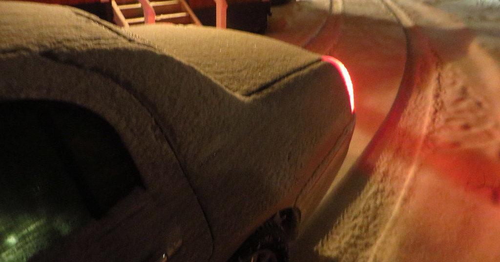A snow-covered car drives through winter weather at night