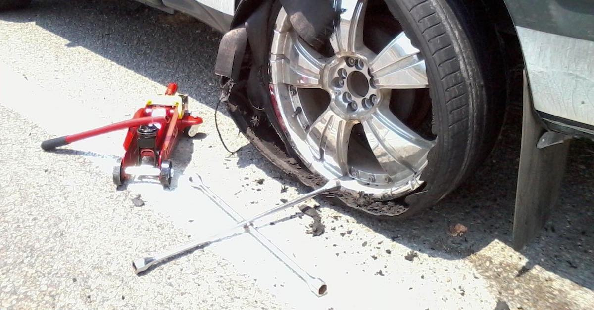 A wrench and jack on the ground next to a car with a flat tire