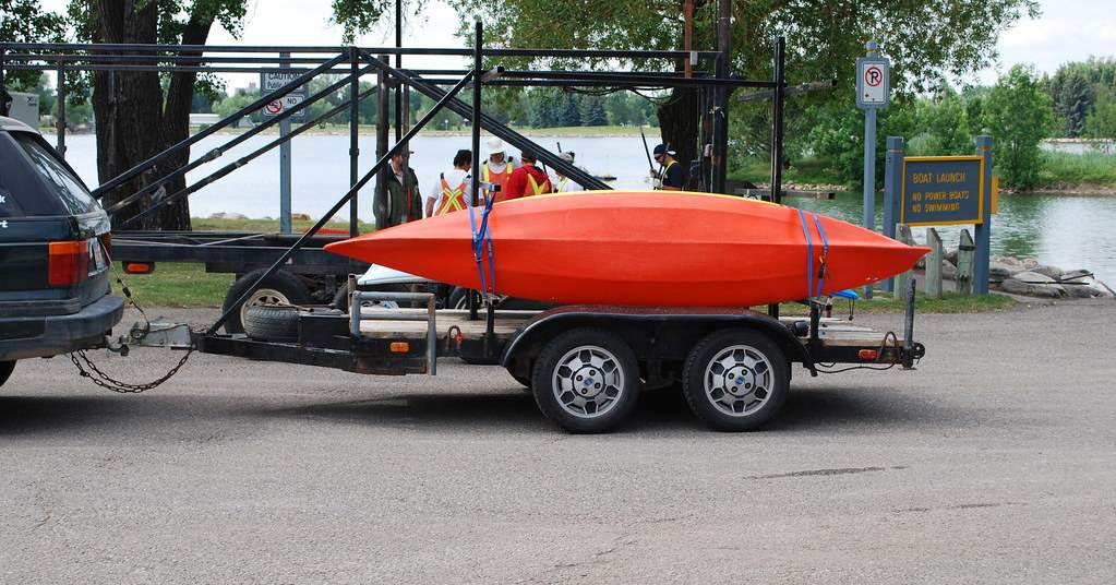 A red canoe loaded onto a truck trailer by a river