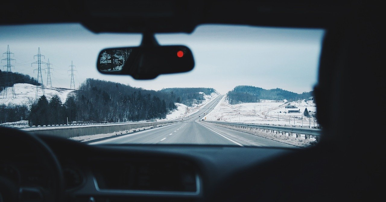 View of a road and snowy landscape through a car's windshield