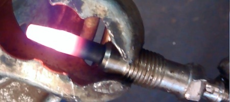 Heated glow plug pulled from diesel engine