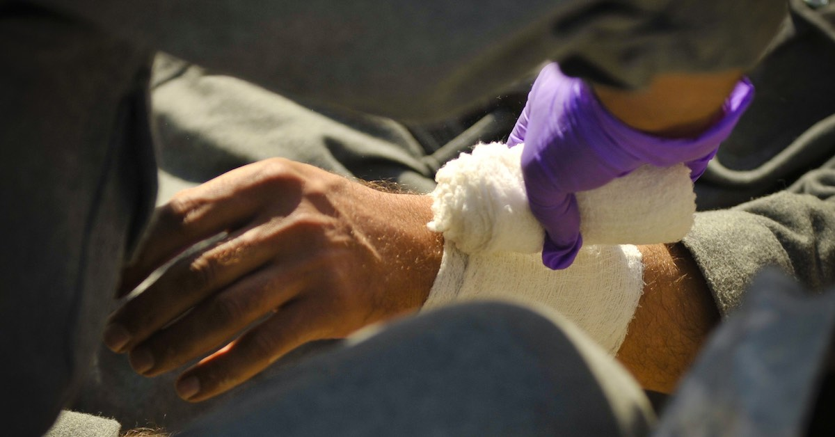 Close-up of a person with purple gloves bandaging another person's wrist