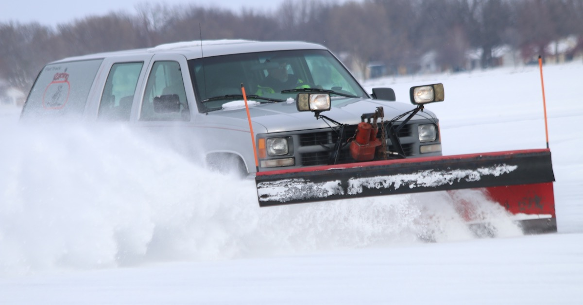 Truck with snowplow attached driving through snow