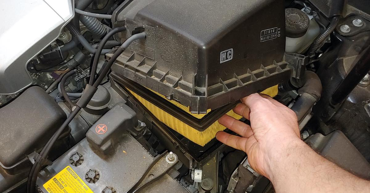 A person opening the engine air filter box under a car's hood
