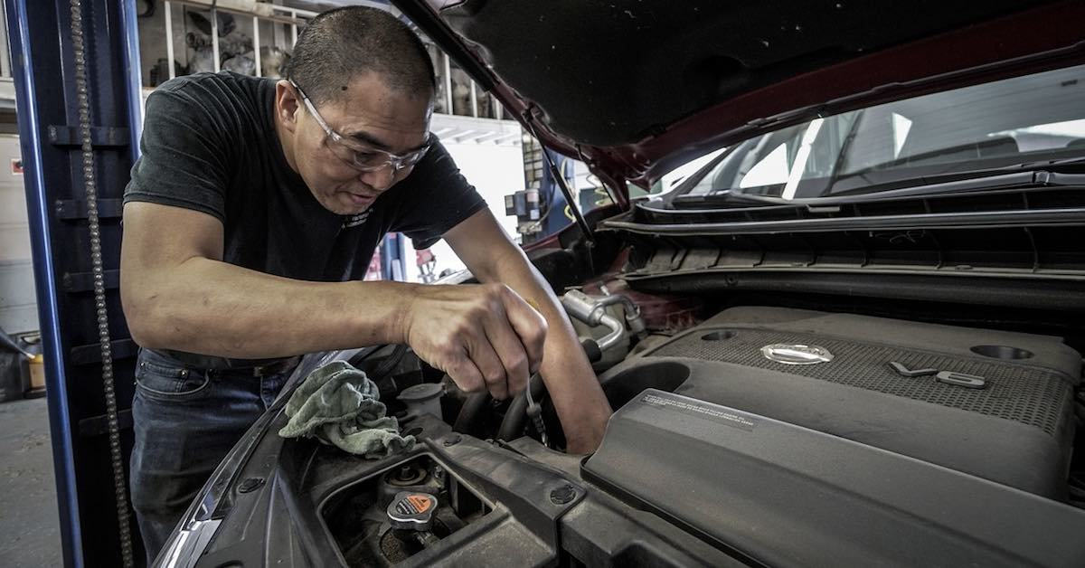 Mechanic wearing protective glasses changing a car's oil