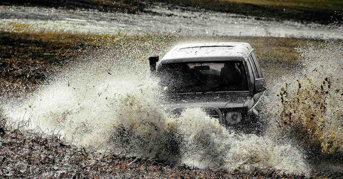 Off-road vehicle splashing through water and mud