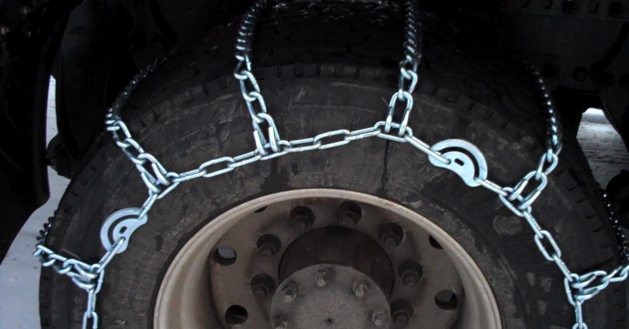 Close-up of a tire encased in a snow chain