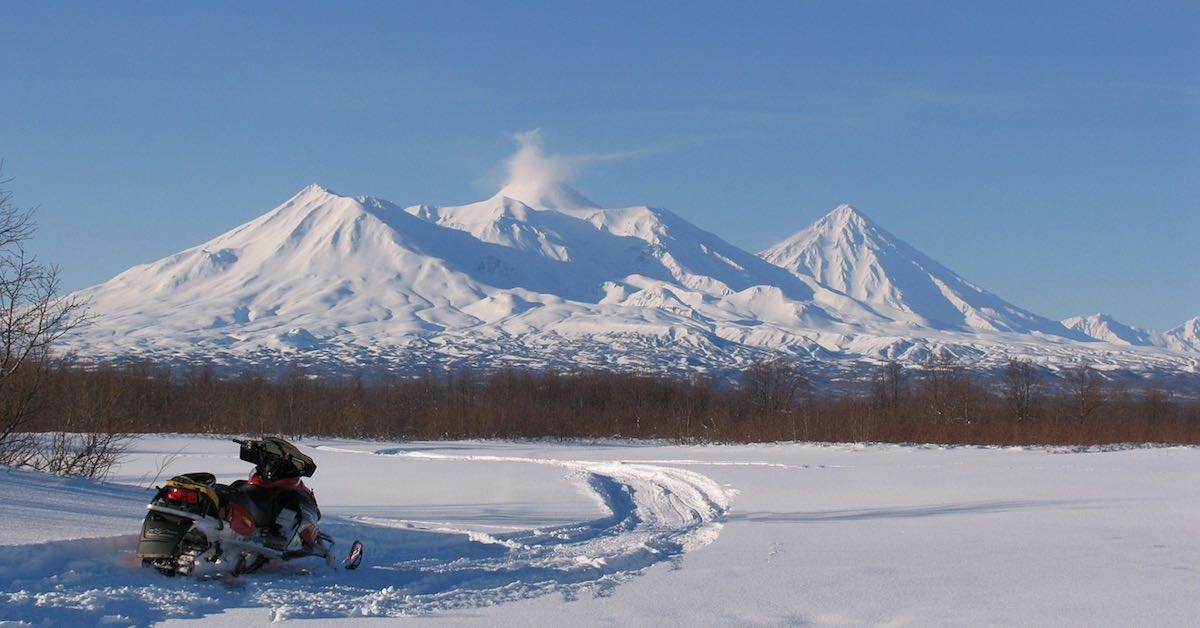 A red and black snowmobile in a snowy, mountainous landscape