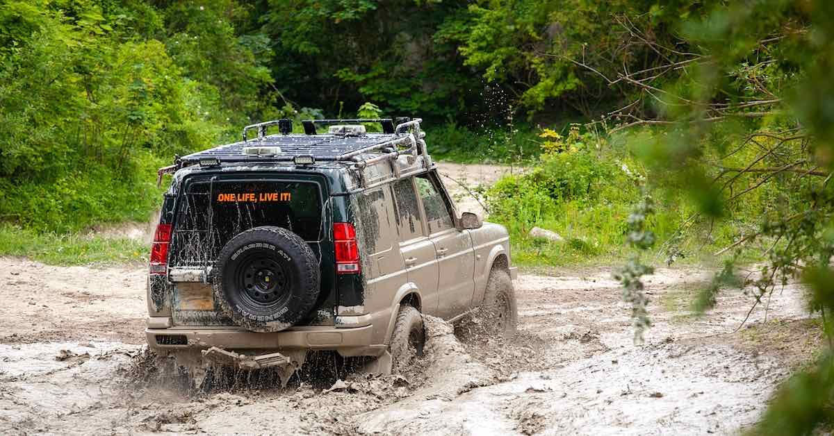 A mud-covered off-road vehicle driving through mud, surrounded by trees