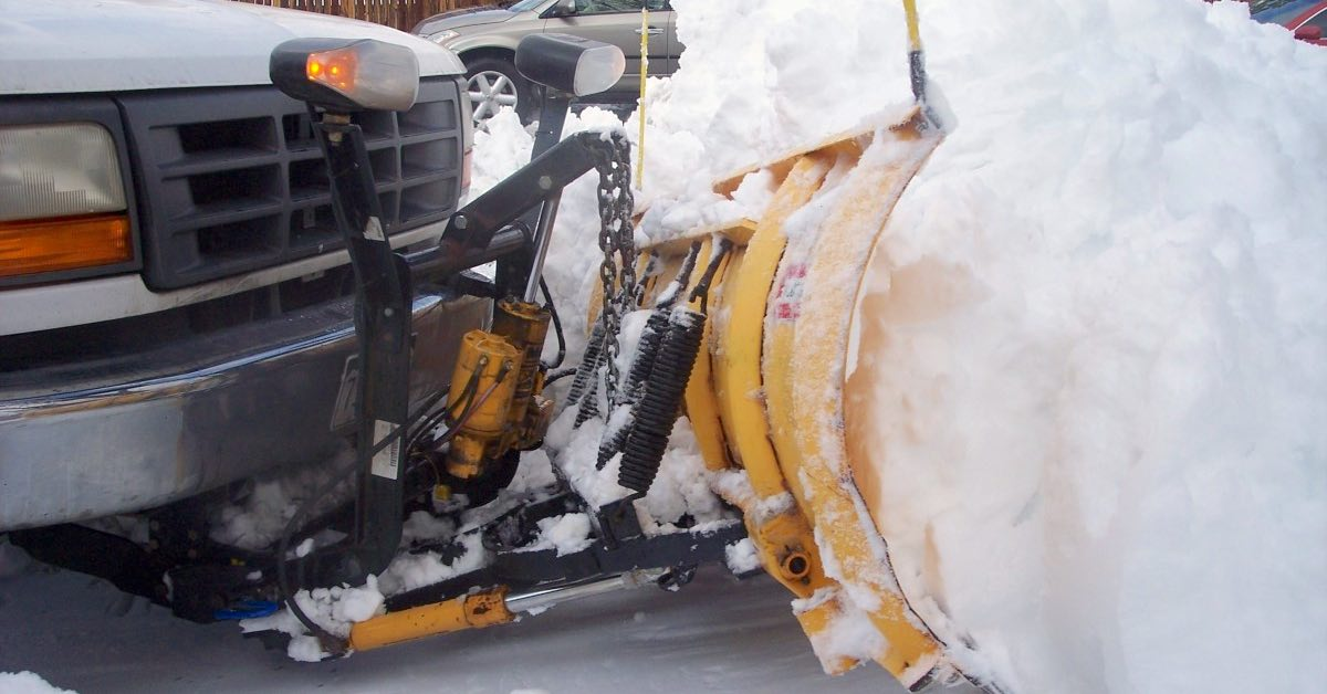Close-up of a white truck with a yellow snowplow moving snow