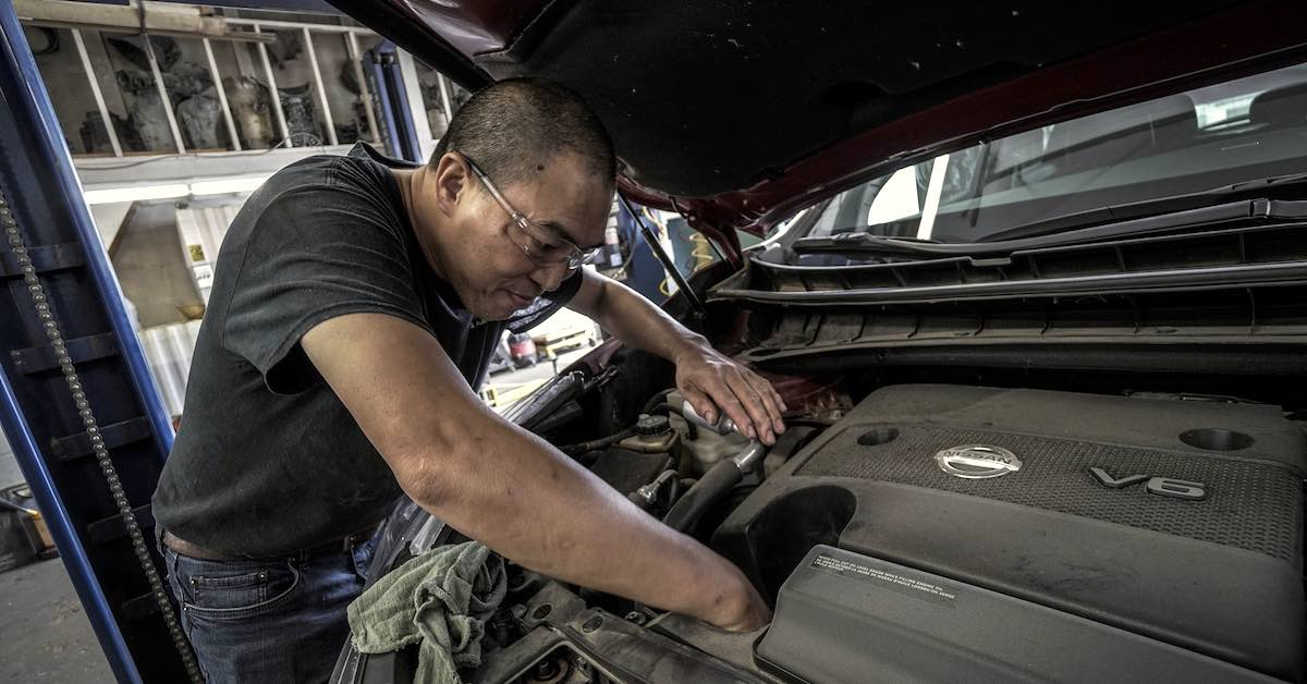 An automotive mechanic reaches to out-of-the-way places under a vehicle's hood
