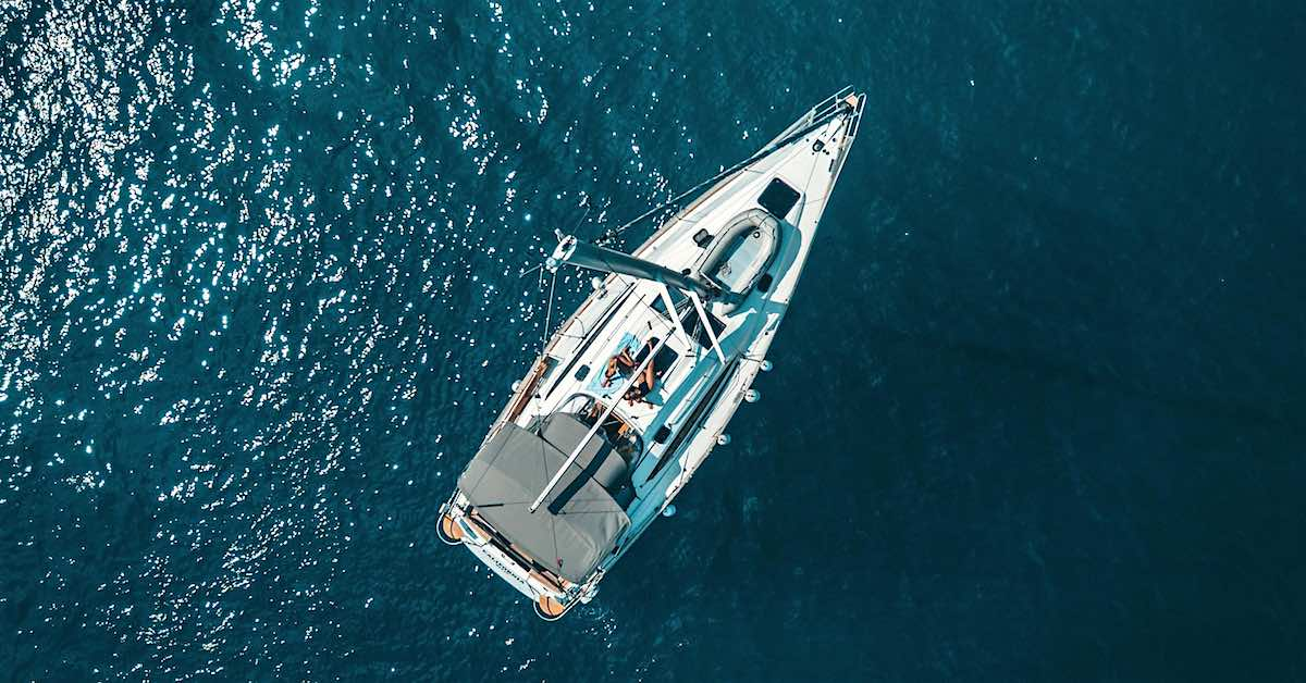 Overhead view of a white boat sailing through blue water