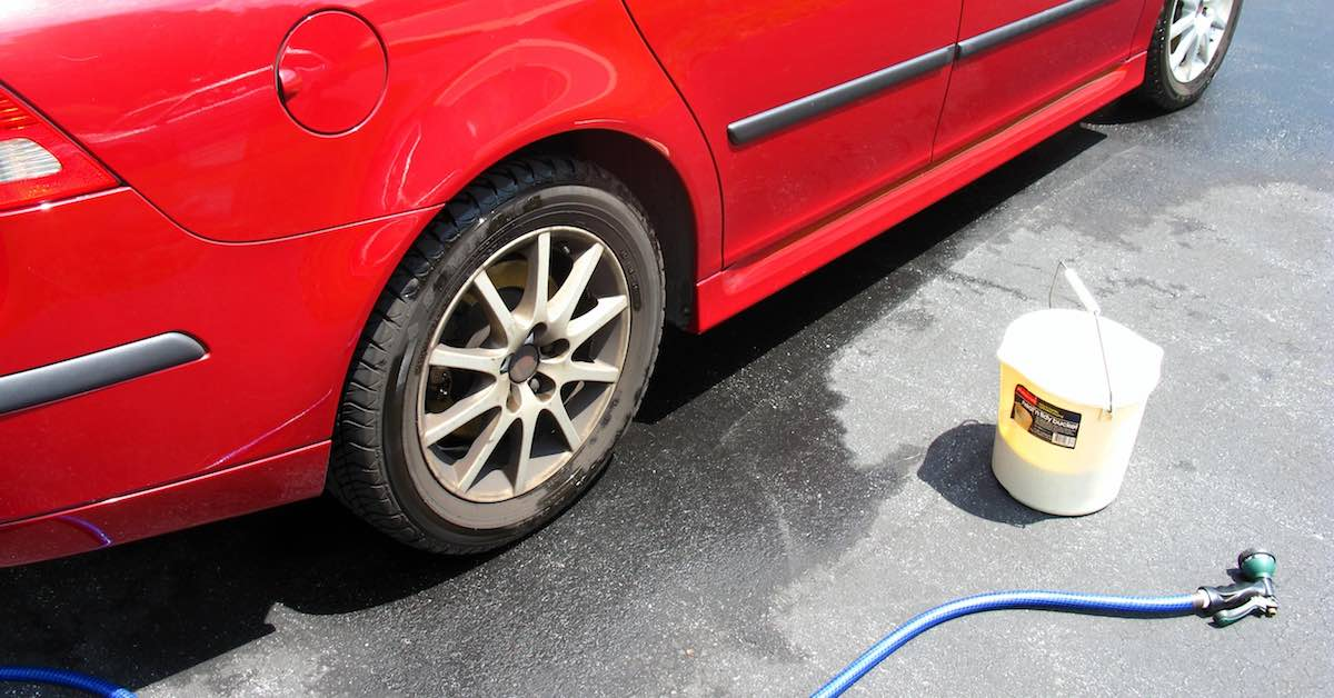 A bucket and hose on the ground by a red car