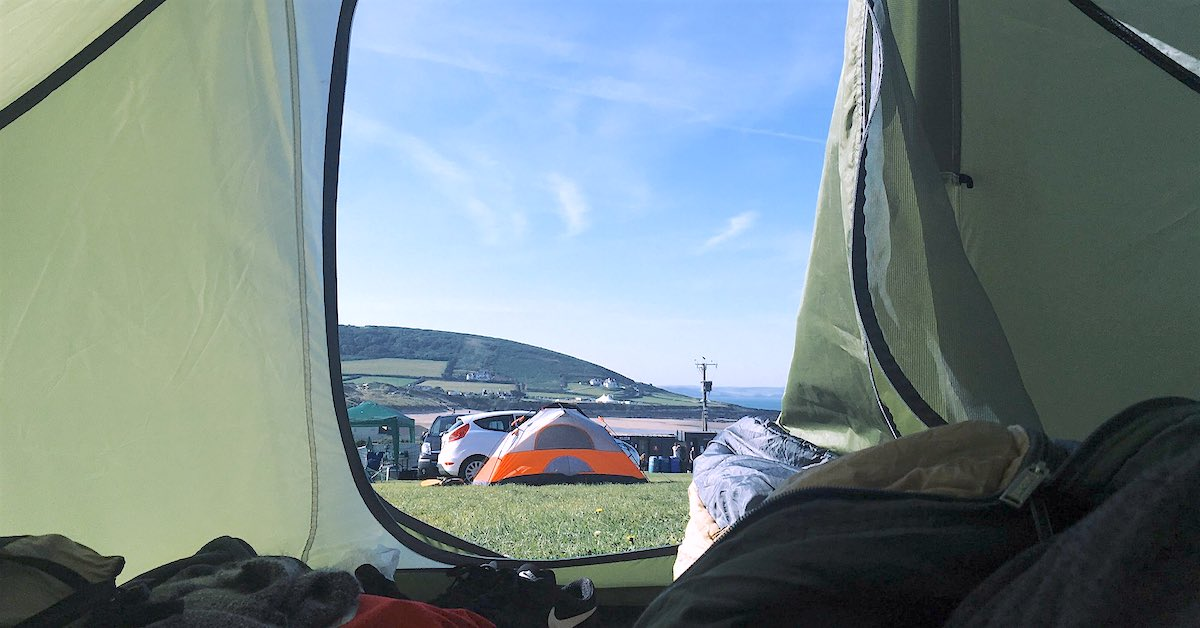 Looking out a green tent onto a landscape with cars and tents