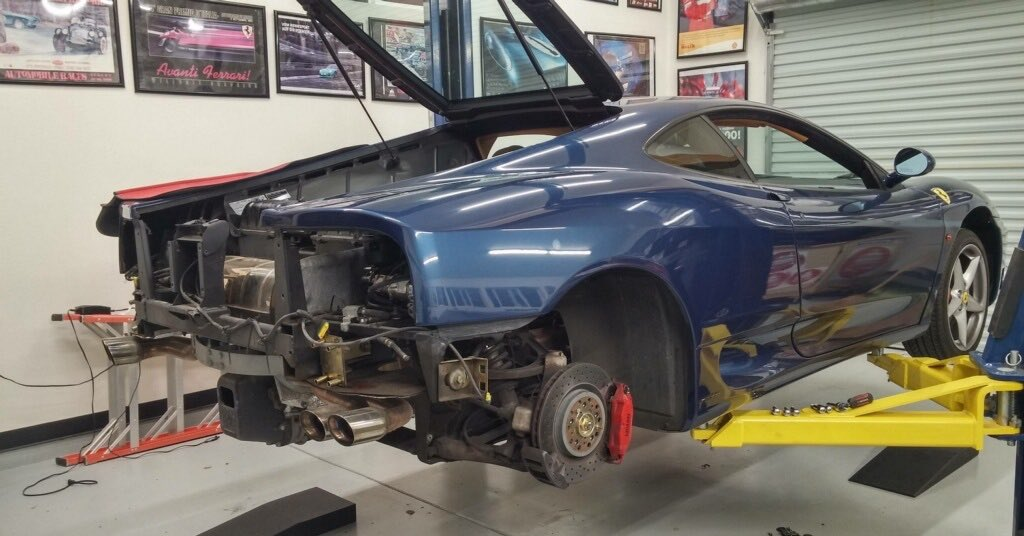 Blue sports car opened up on a yellow car lift in a garage