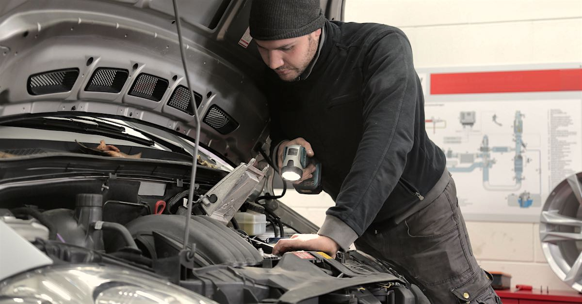 Man in black jacket and knit cap inspecting a car engine