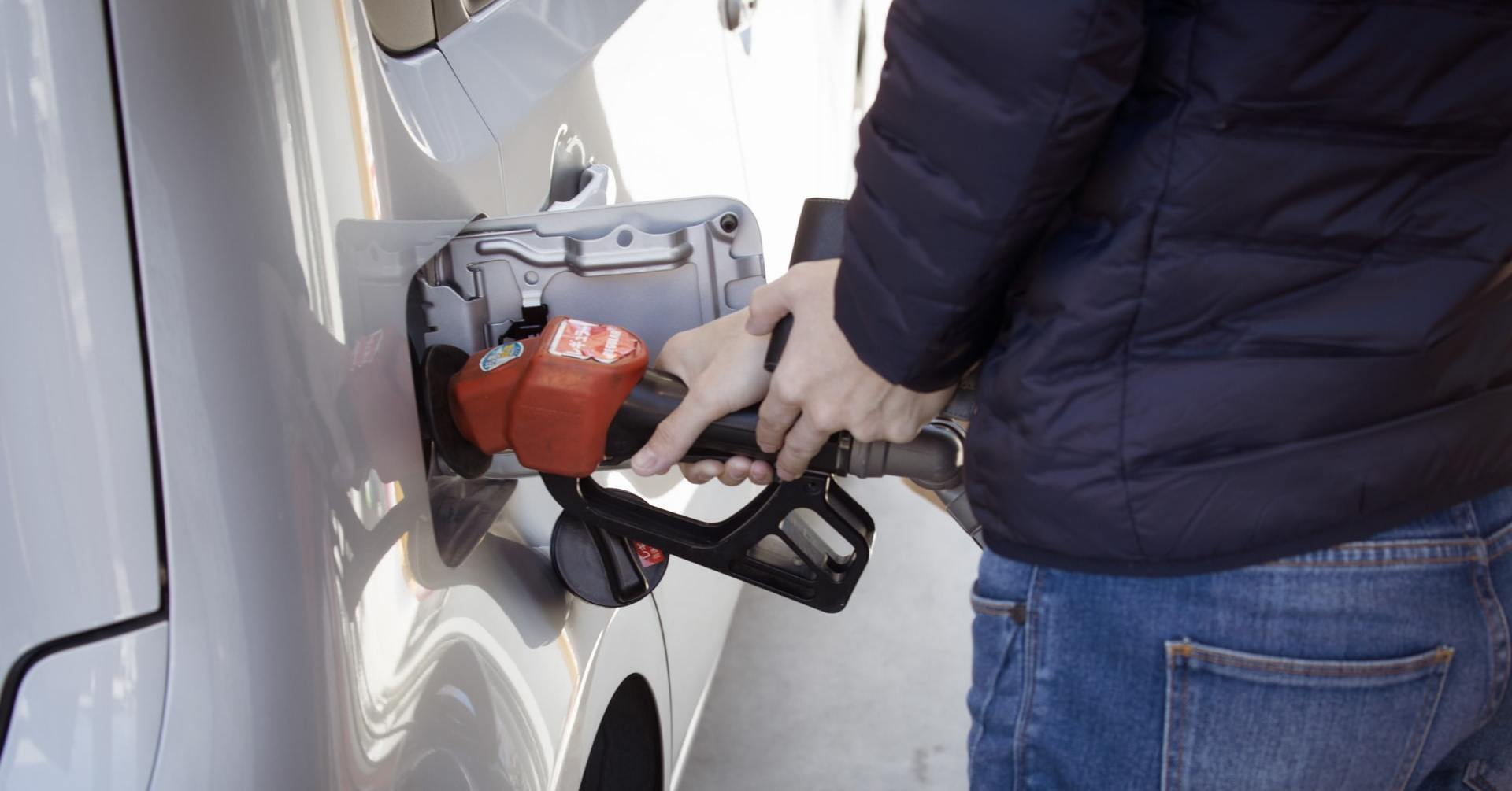 A person in a black coat and jeans putting gas in their car