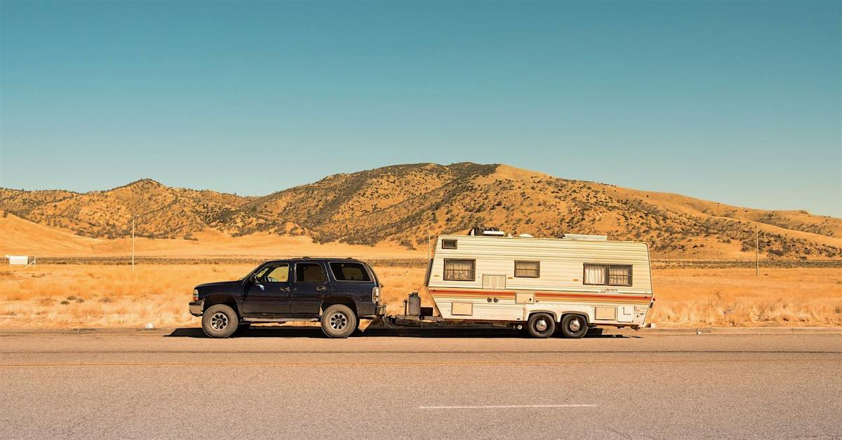 Black SUV towing a trailer in the desert