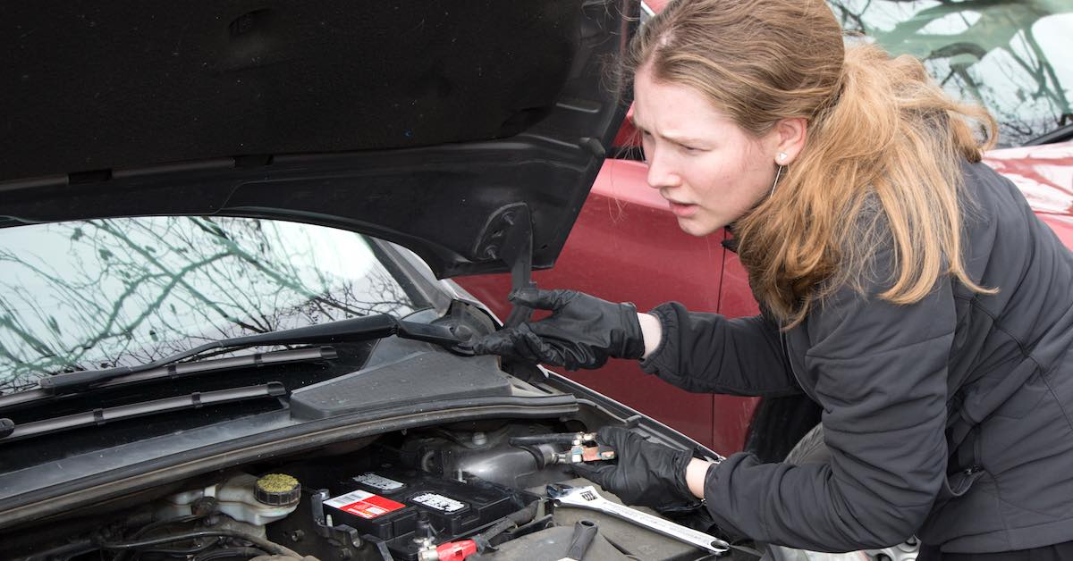 A woman wearing gloves looking under a car's hood