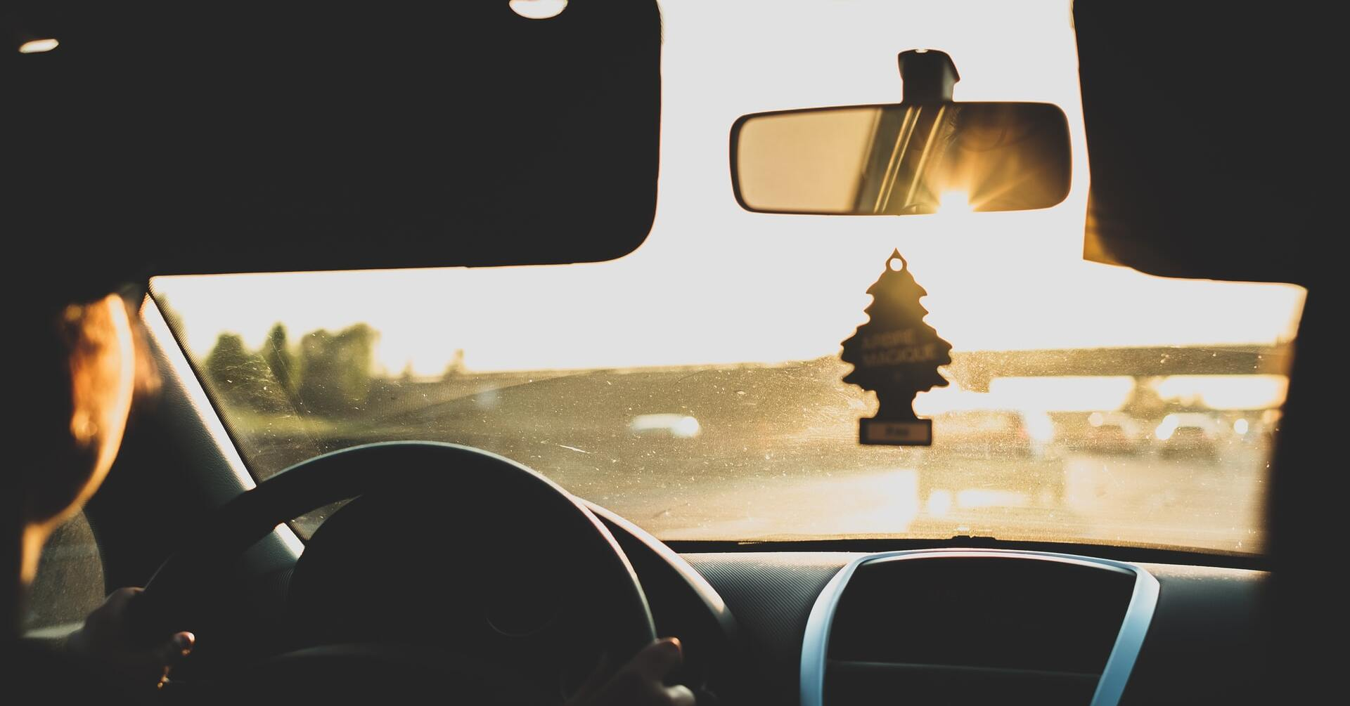 An air freshener hangs from a car's rearview mirror
