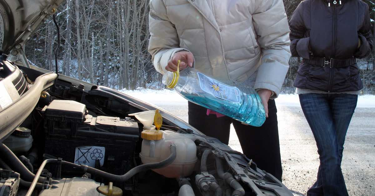 Adding antifreeze to an engine in a snowy landscape
