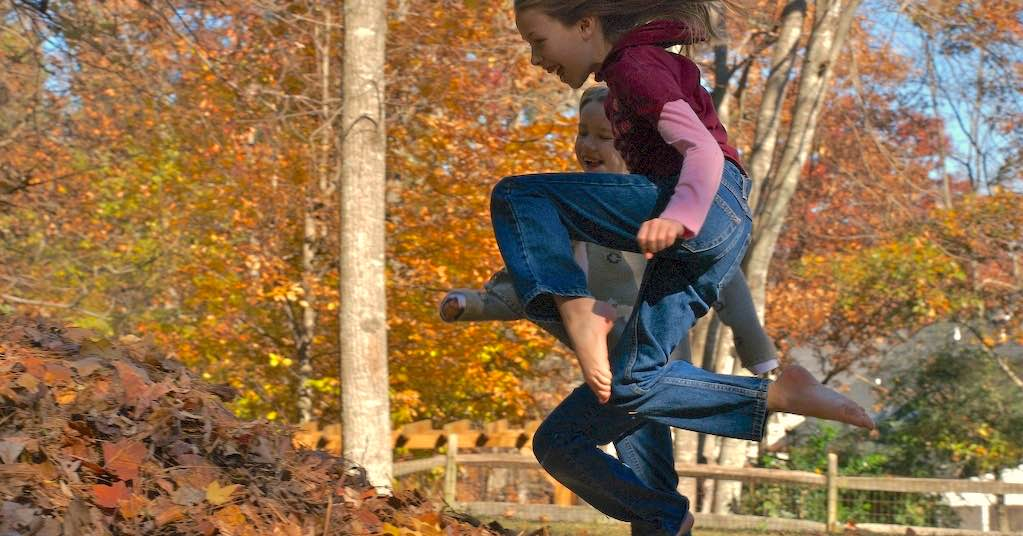 Two girls jump into a pile of autumn leaves
