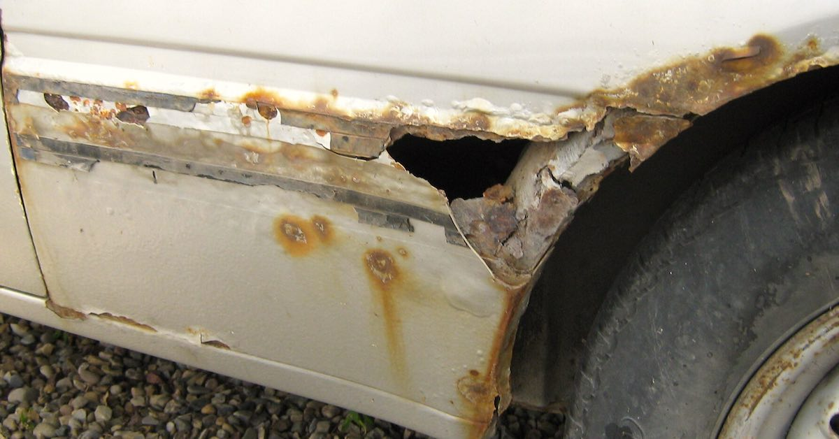 The fender of a car shows significant rust damage near the wheel well.