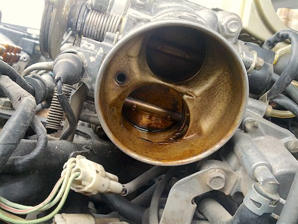This throttle body features an idle air control valve mounted on the side.