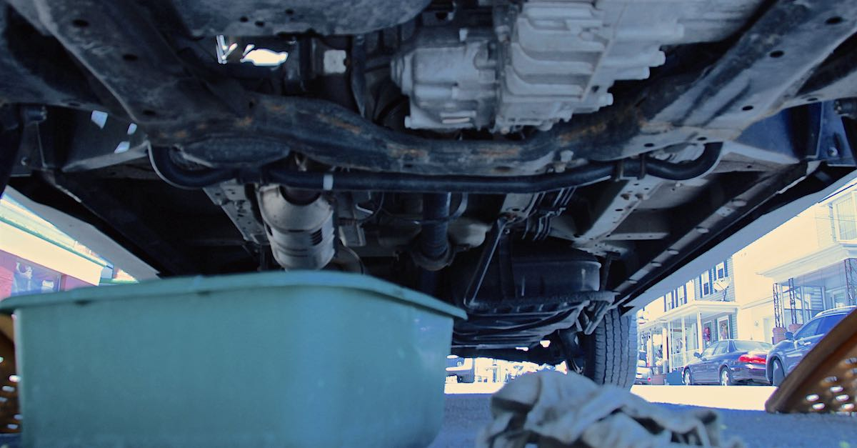 Oil drains from a car during an oil change.