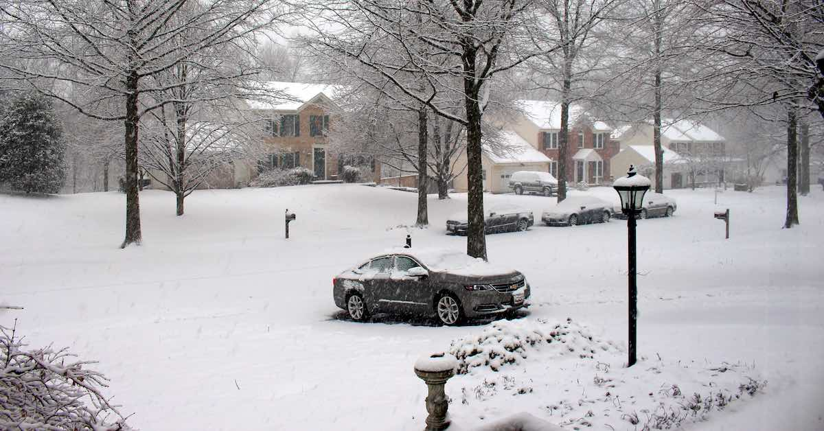 A sedan parked in a driveway on a snowy day.