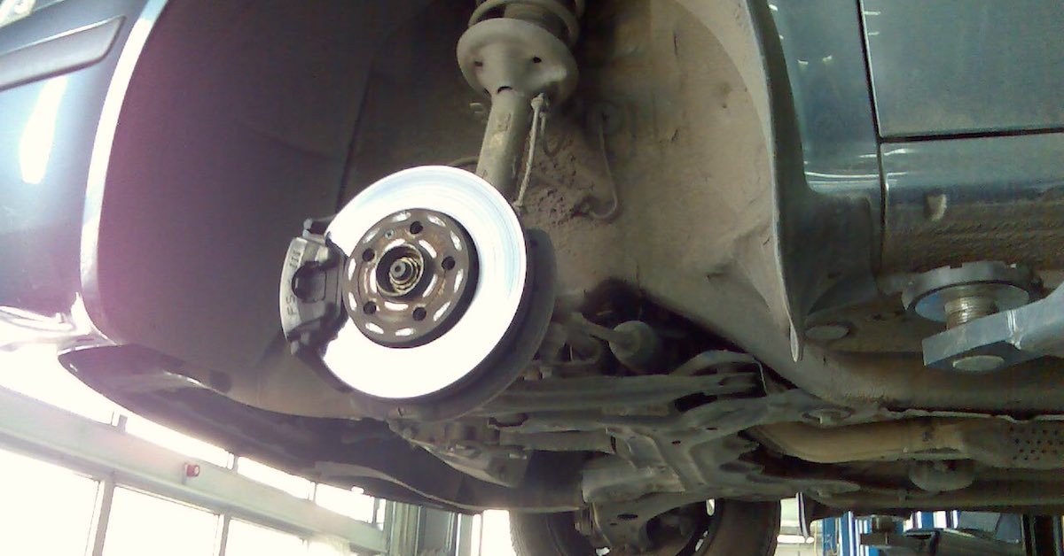 An exposed brake, rotor and caliper that needs to be cleaned of dust and grime.