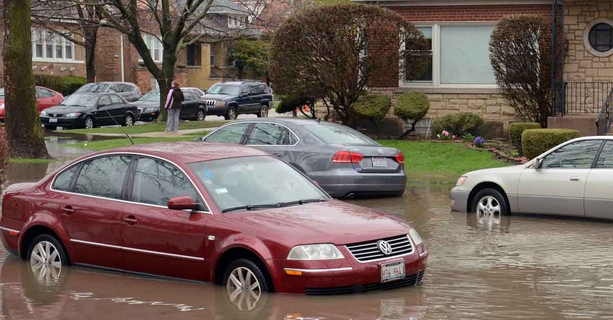 A sedan in a flooded area faces potential water damage and mold problems.