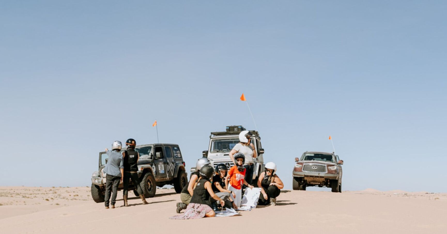 Rebelle Rally competitors navigate through sand dunes.
