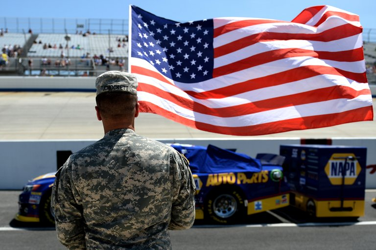 DOVER, DE - JUNE 02: A service member holds the American flag during pre-race ceremonies for the NASCAR Sprint Cup Series FedEx 400 benefiting Autism Speaks at Dover International Speedway on June 2, 2013 in Dover, Delaware. (Photo by Patrick Smith/Getty Images)