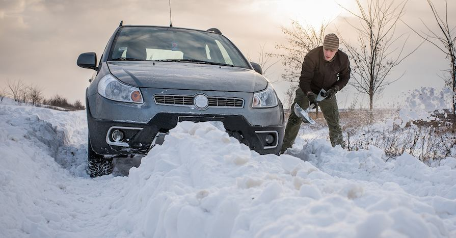 man digging up stuck in snow car