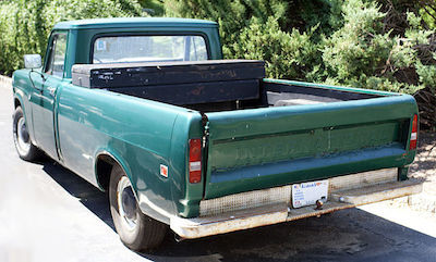 An iconic International pickup truck suffers from rust at the base of the liftgate.