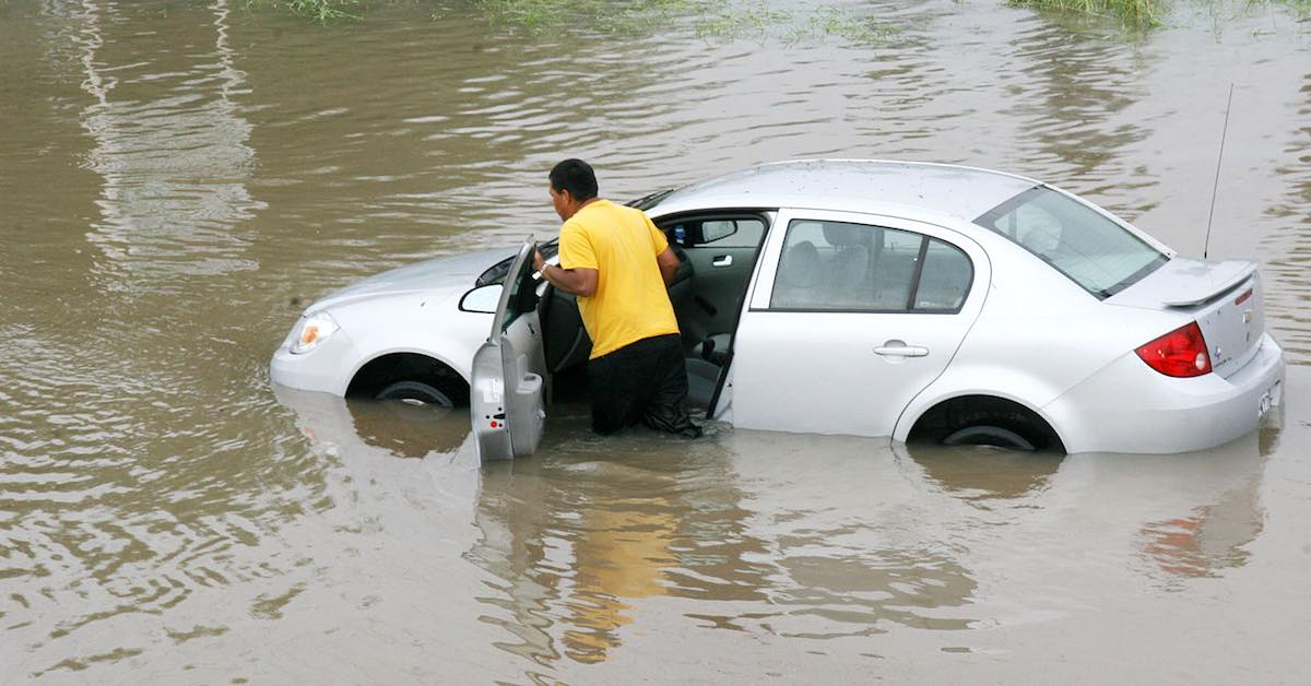 Man pushes flooded car through deep water.