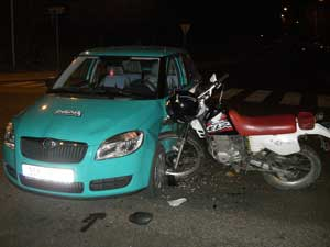 A motorcycle crashed into the side of a car.