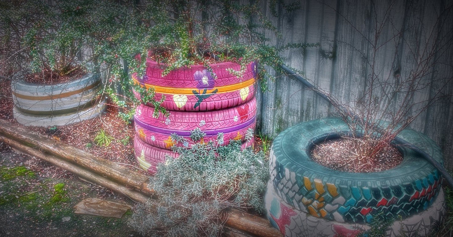 Tires stacked up and used as a planter in a garden. spare car parts