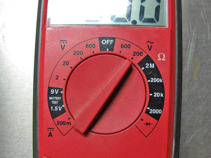 The dial is set to Volts AC in the 200 range.